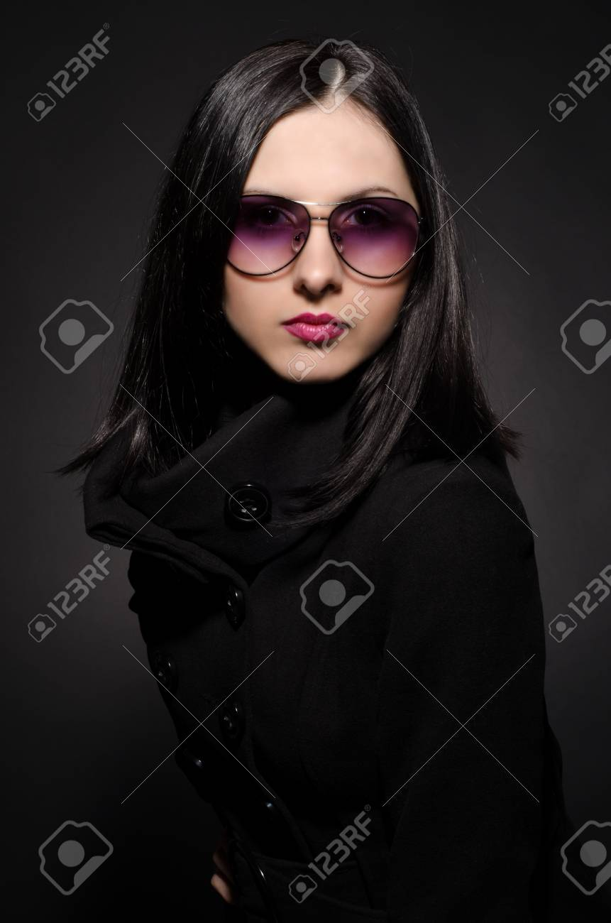 Portrait of a beautiful young woman in sunglasses on black background Stock Photo - 17573353