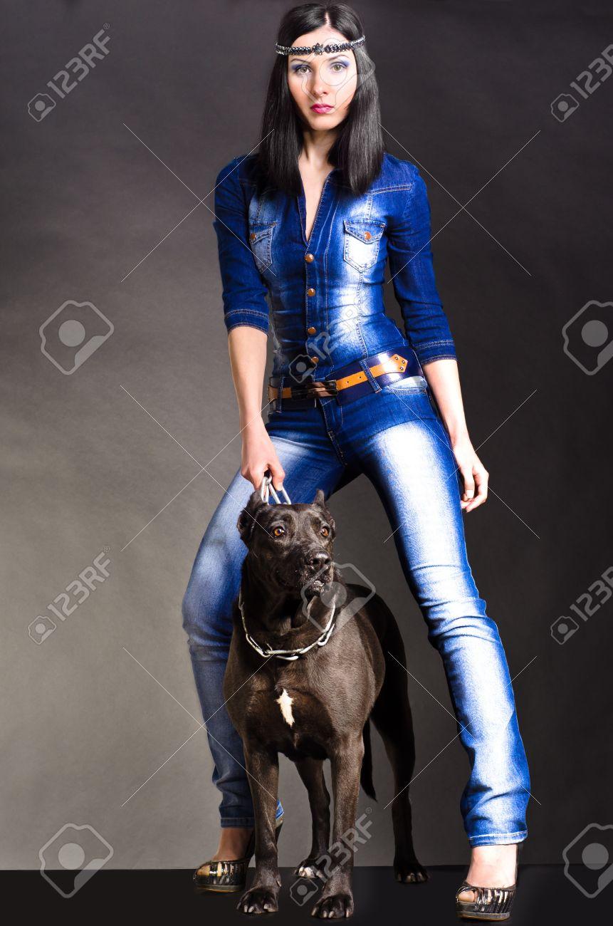 mujer hermosa en ropa de mezclilla de pie junto a un perro foto de archivo