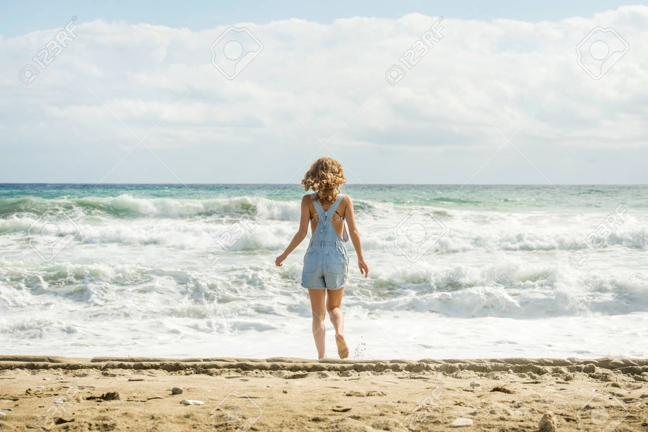 ac660e59b57b Young woman in blue denim jumpsuit walking towards stormy sea Stock Photo -  58853520