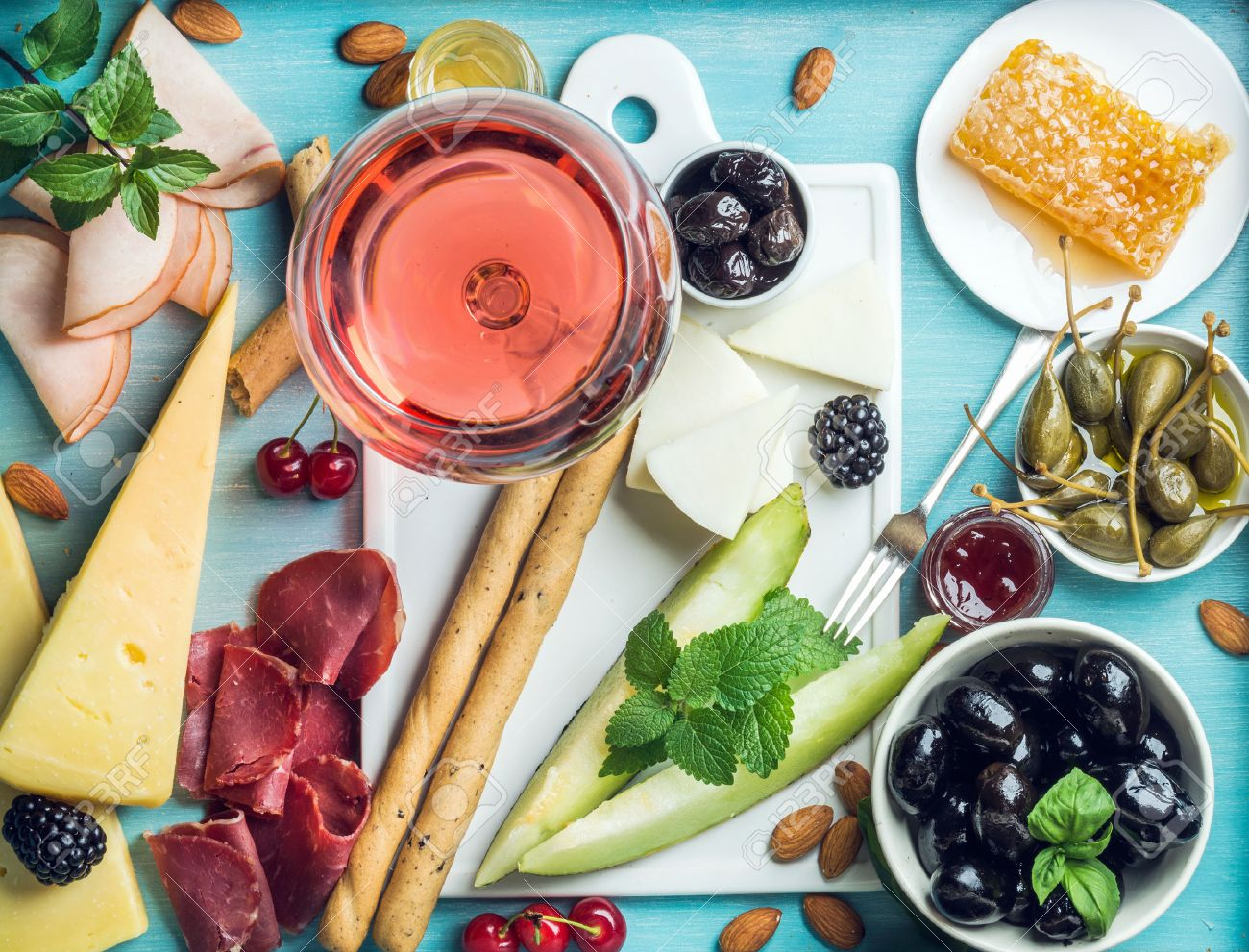 Summer wine snack set. Glass of rose, meat, cheese, olives, honey, bread sticks, nuts, capers and berries with white ceramic board in center, blue wooden background, top view - 58853529