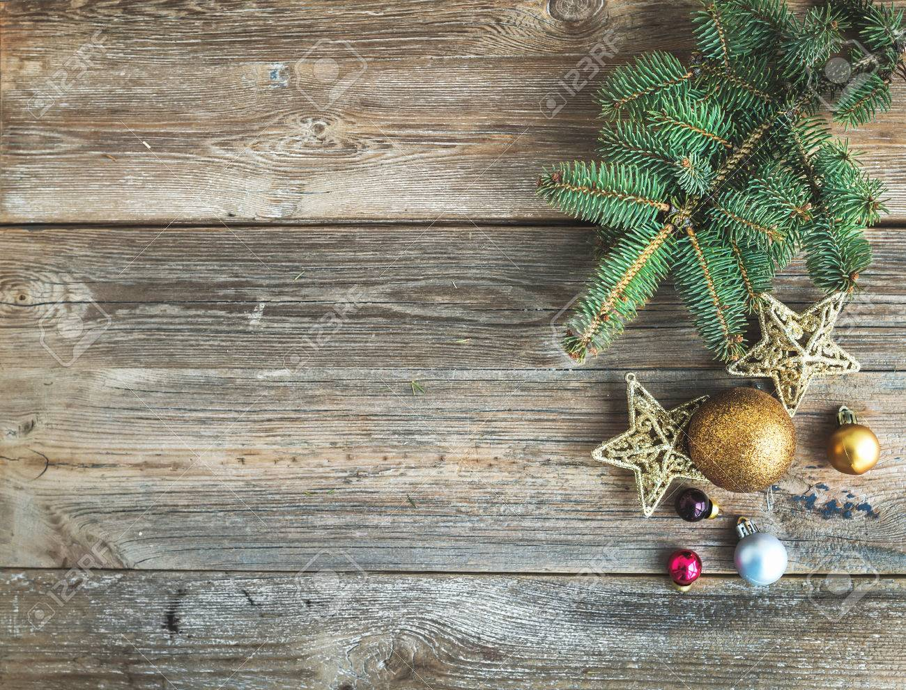 Christmas Or New Year Rustic Wooden Background With Toy Decorations And Fur Tree Branch Top