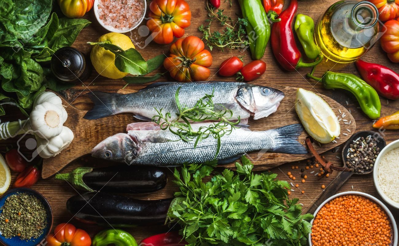 Raw uncooked seabass fish with vegetables, grains, herbs and spices on chopping board over rustic wooden background, top view - 58854348