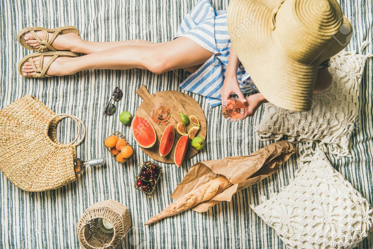 725a641303e Summer picnic setting. Woman in linen striped dress and straw sunhat  sitting with glass of rose wine in hand