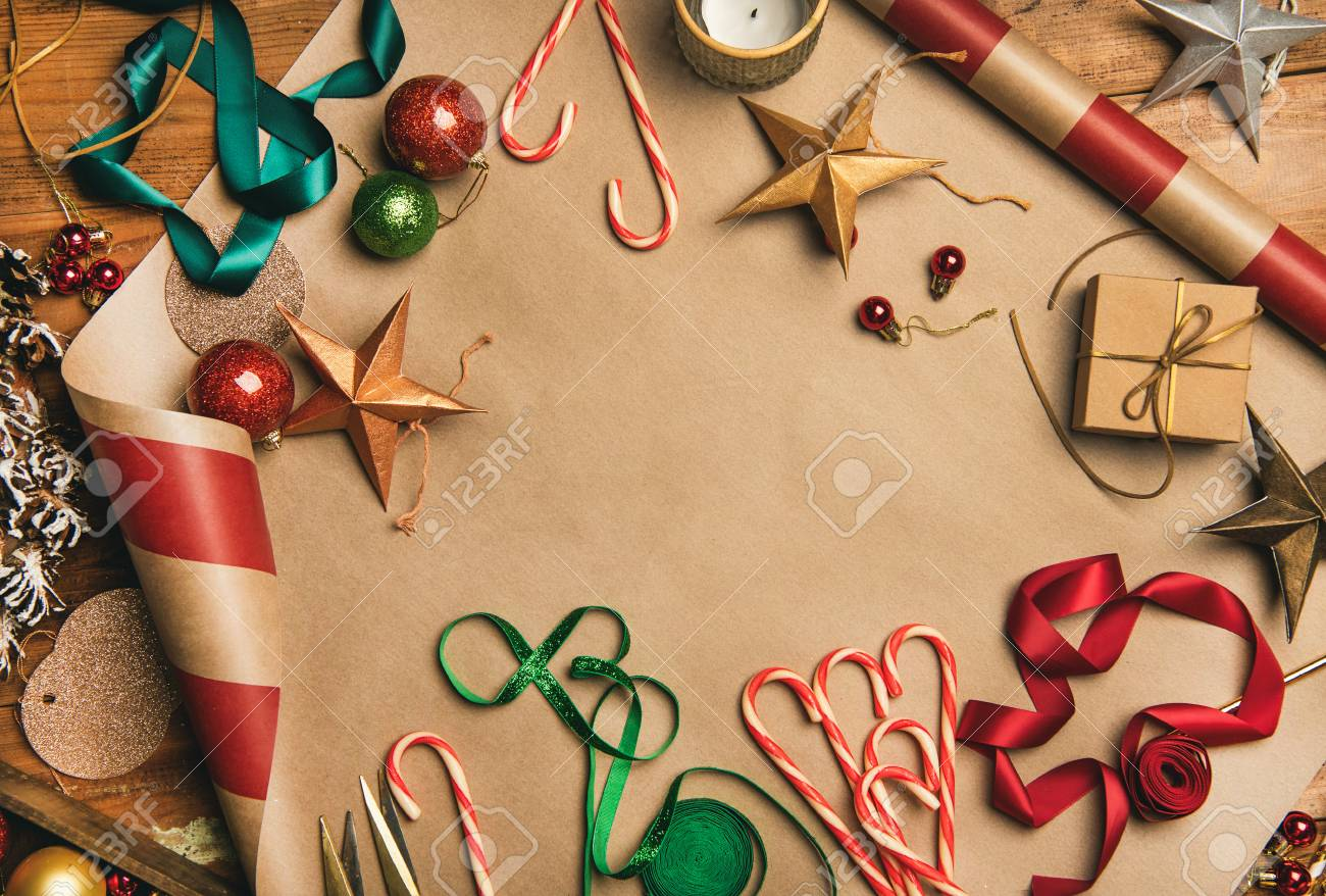 Getting ready for Christmas or New Year holiday. Flat-lay of decorations, ribbons, gift paper, door wreath, glittering balls, candy canes, top view, copy space. Christmas festive mood - 112415205