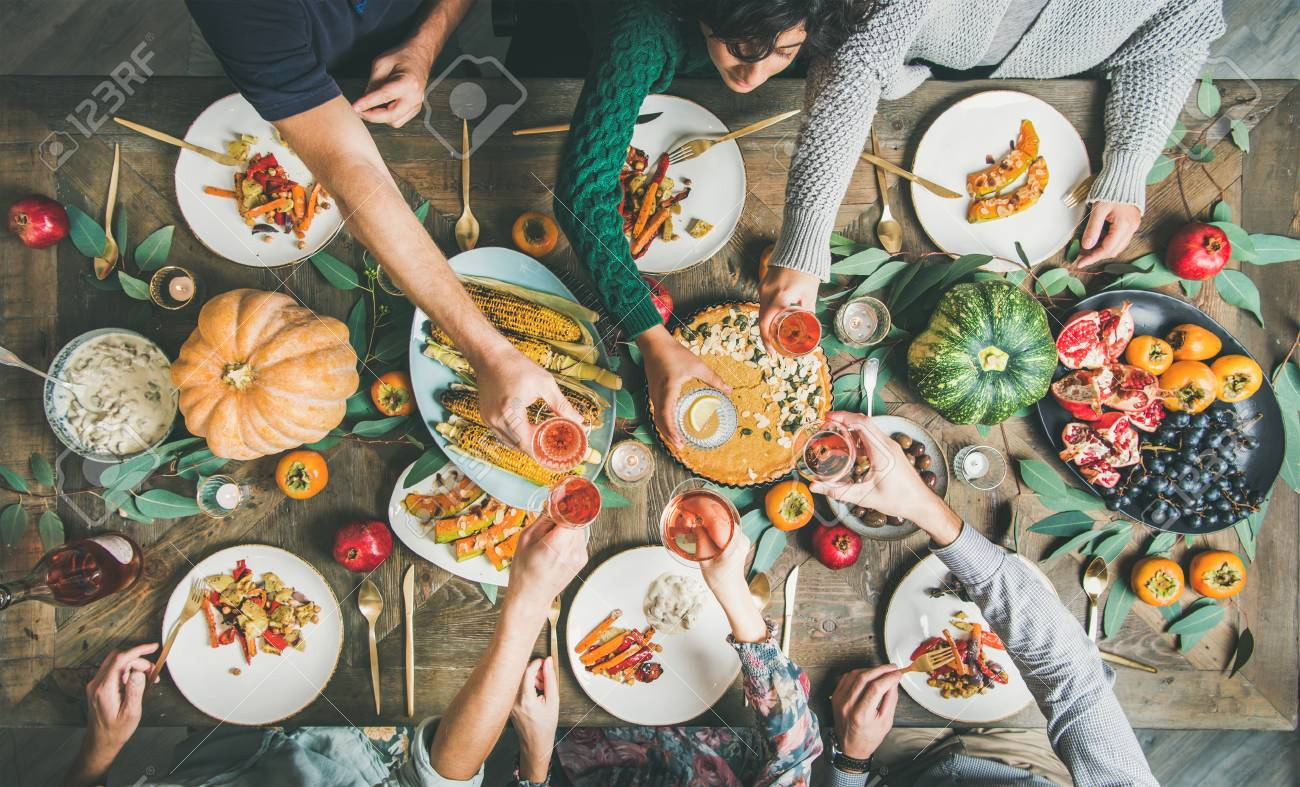 Vegan or vegetarian Thanksgiving, Friendsgiving holiday celebration. Flat-lay of friends eating and clinking glasses at Thanksgiving Day table with pumpkin pie, vegetables, fruit and wine, top view - 113573511