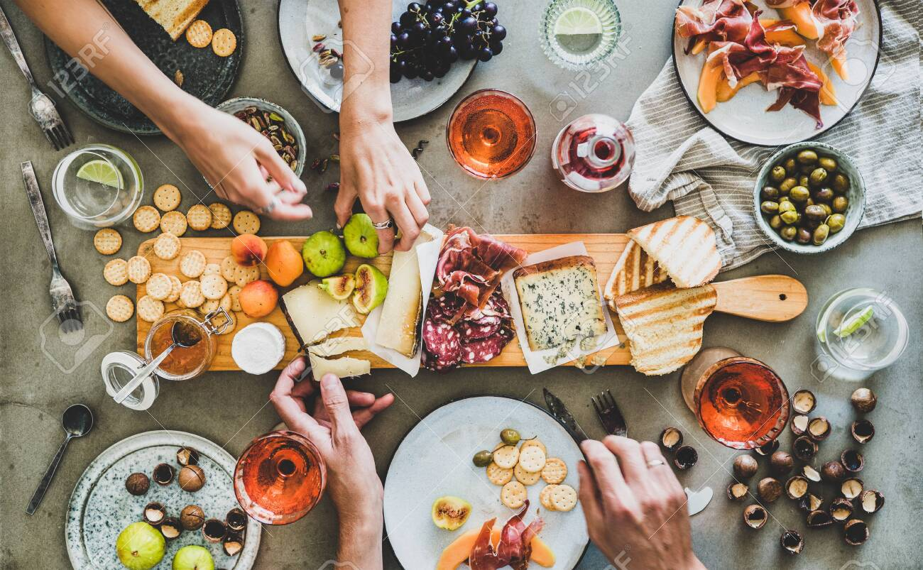 Mid-summer picnic with wine and snacks. Flat-lay of charcuterie and cheese board, rose wine, nuts, olives and peoples hands over concrete table background, top view. Family, friends holiday gathering - 128434895