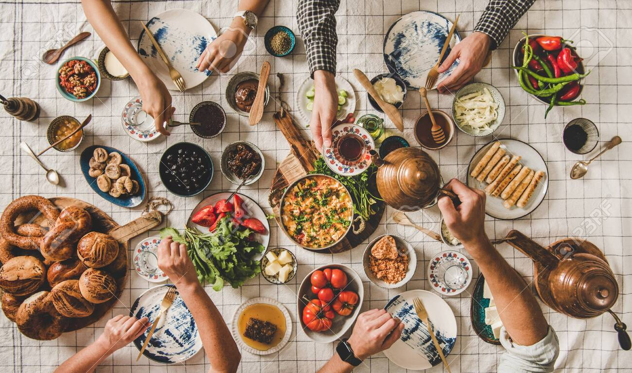 Flat-lay of family having Turkish breakfast with fresh pastries, vegetables, greens, spread, cheeses, fried eggs, jams and tea in tulip glasses and copper teapots over pastel chekered linen tablecloth - 134333210
