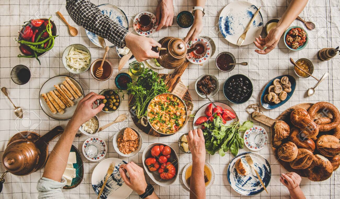 Flat-lay of family having Turkish breakfast with pastries, vegetables, greens, spreads, cheeses, fried eggs, jams and tea in tulip glasses and copper teapots over pastel chekered linen tablecloth - 137688738