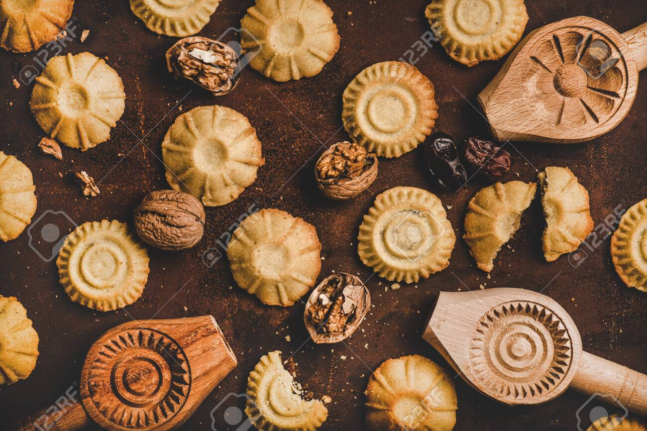 Flat-lay of Turkish traditional Hatay semolina cookies with date, fig, walnut filling and wooden cookie baking molds over rusty dark background, top view. Middle East regional east Anatolian cuisine - 139068798
