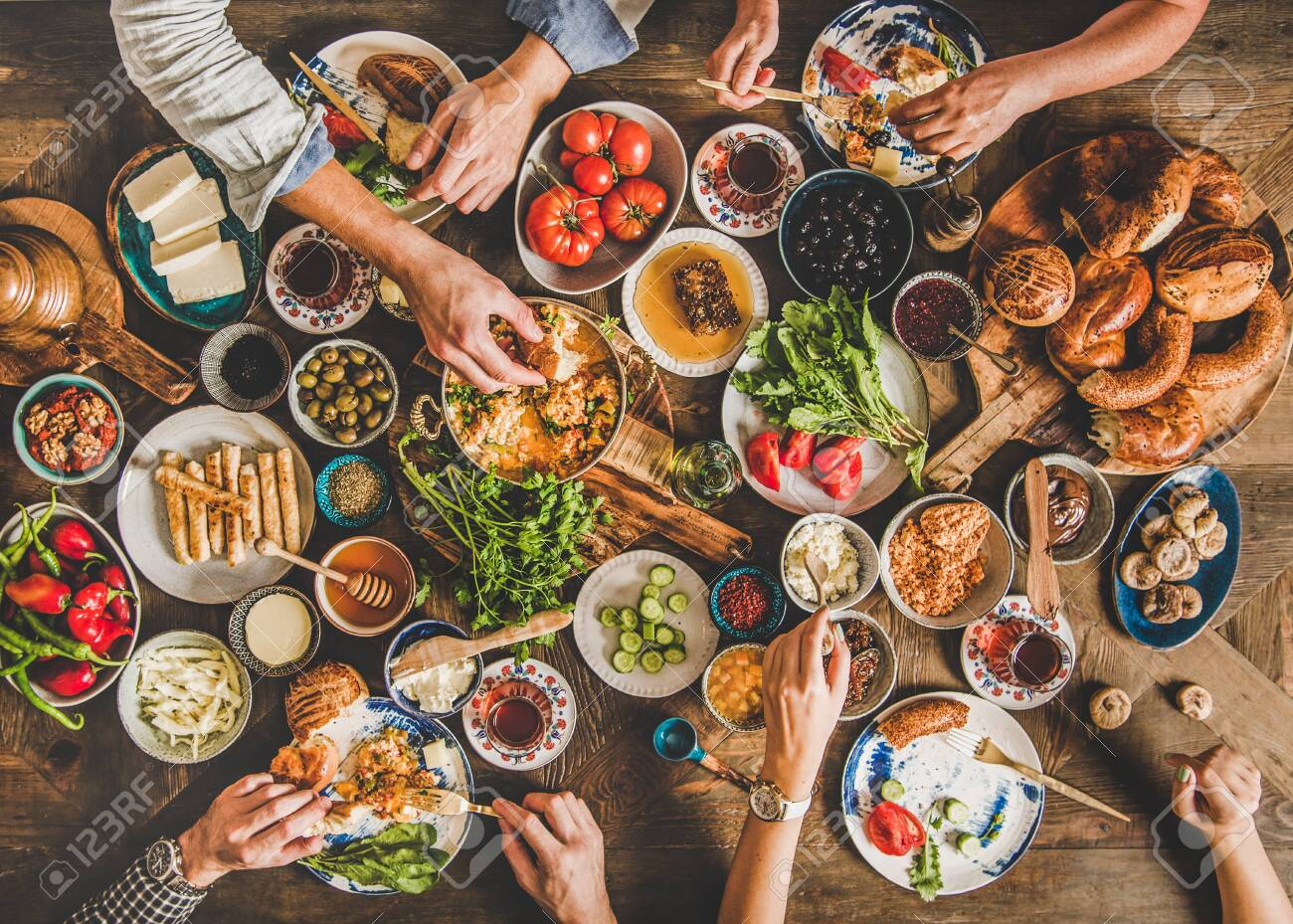 Turkish breakfast table. Flat-lay of peoples hands taking Turkish pastries, vegetables, greens, cheeses, fried eggs, jams and tea in copper pot and tulip glasses over wooden background, top view - 139782416