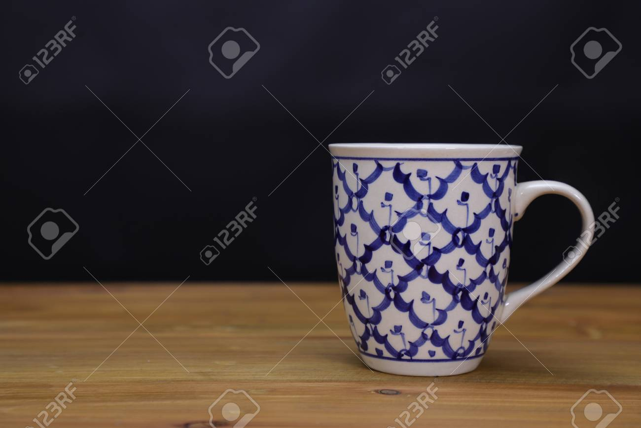2a714c295be Stock Photo - white and blue ceramic coffee mug, on brown wooden background