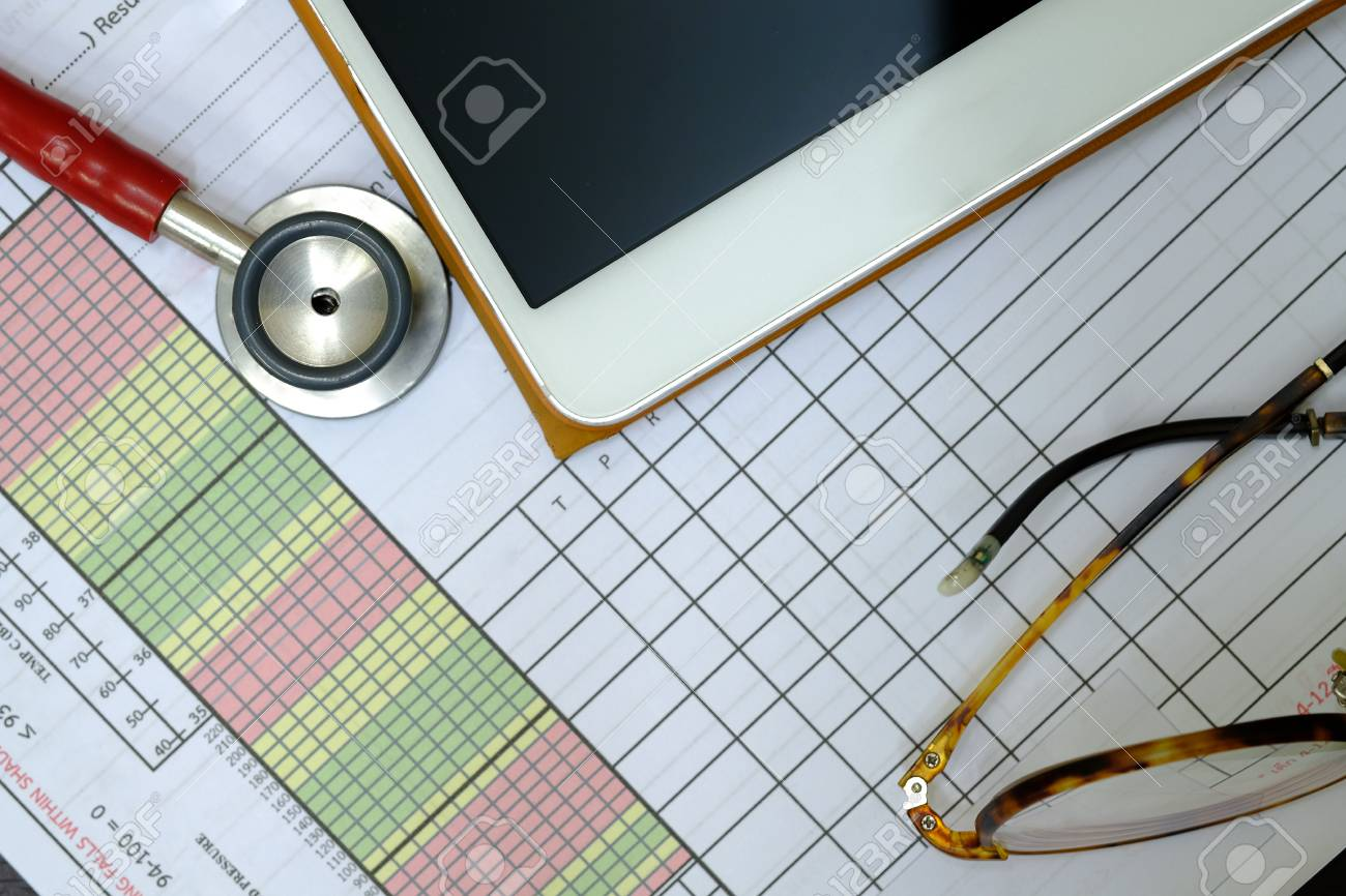a red stethoscope a patient vital sign sheet a tablet and stock