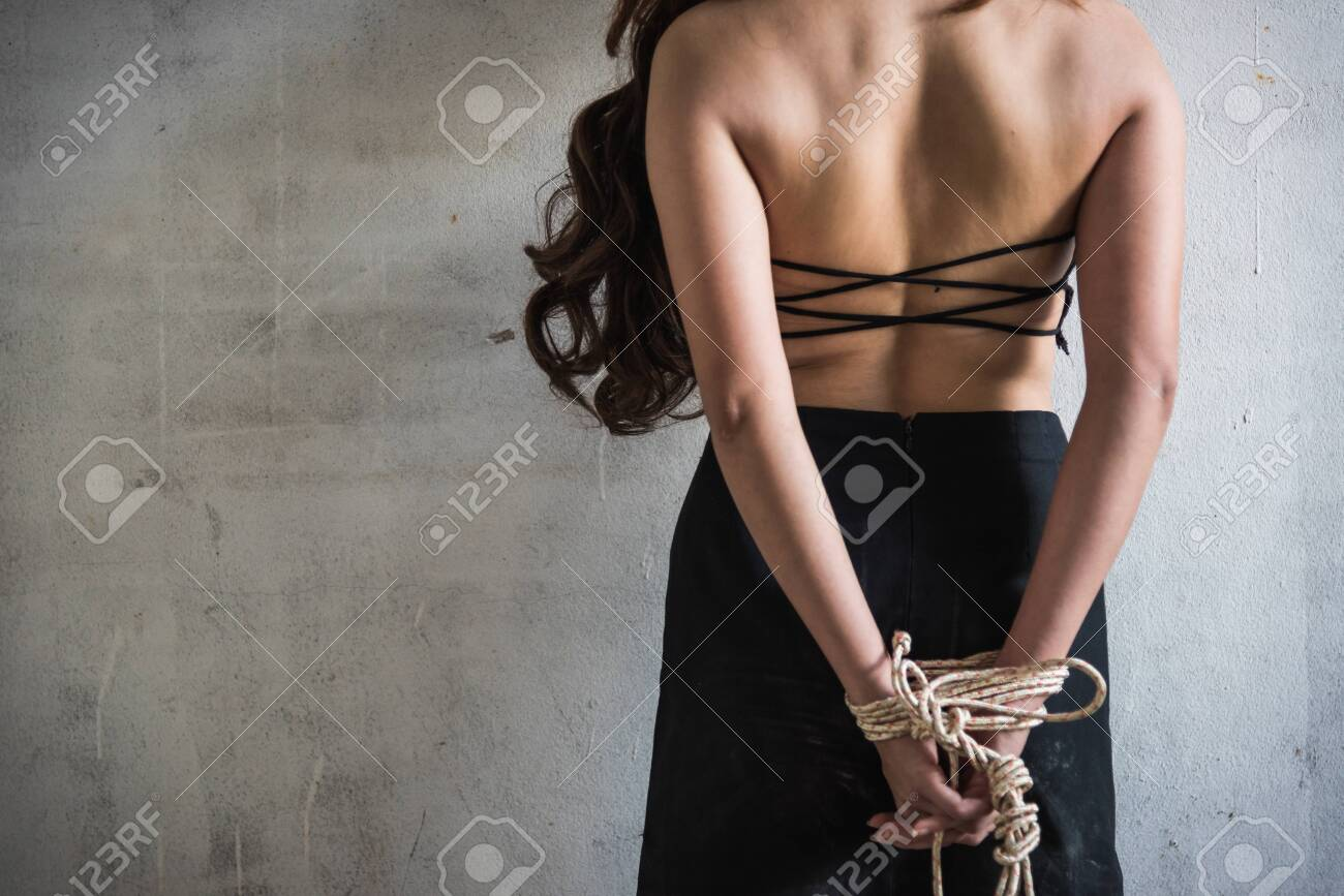 Young woman take off her shirt raping rope tied arm standing facing wall, criminal robber concept with copy space - 130985495