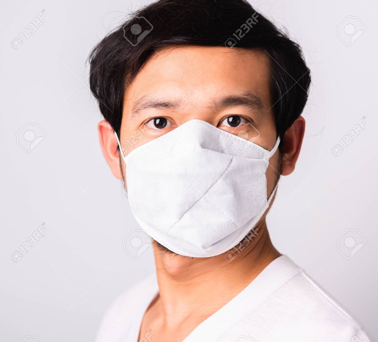 Closeup Asian handsome Man wearing surgical hygienic protective cloth face mask against coronavirus, studio shot isolated white background, COVID-19 medical concept - 145780971