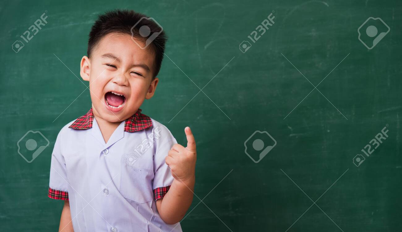 Back to School. Happy Asian funny cute little child boy from kindergarten in student uniform smiling point finger to side away space on green school blackboard, First time to school education concept - 146611439