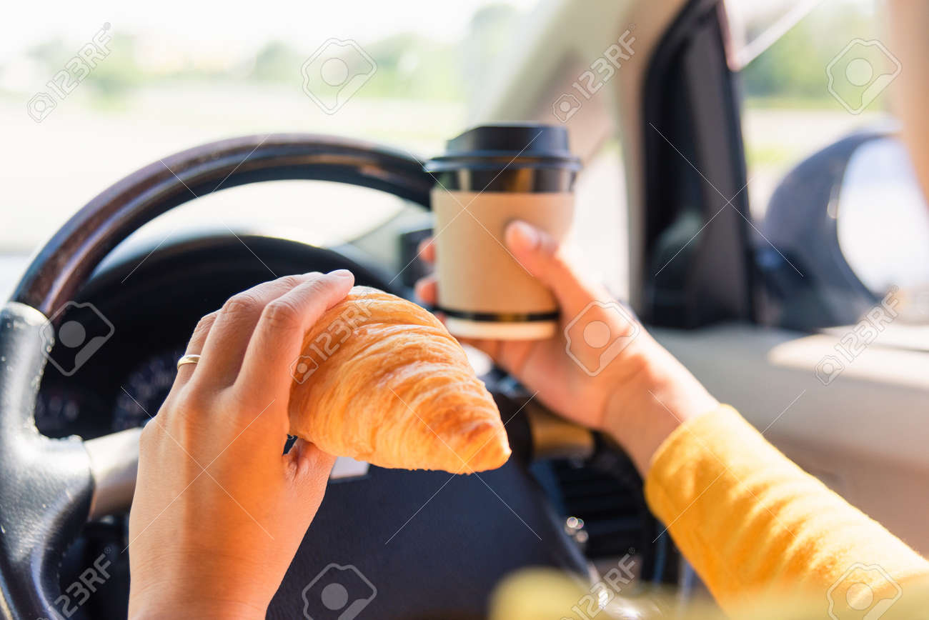 Asian woman eating food fastfood and drink coffee while driving the car in the morning during going to work on highway road, Transportation and vehicle concept - 157444869