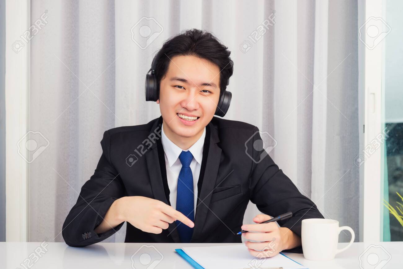 Work from home, Asian young businessman wear suit video conference call or facetime he smiling sitting on desk wearing headphones and raise his hand point finger to a paper job he looking to camera - 159580492
