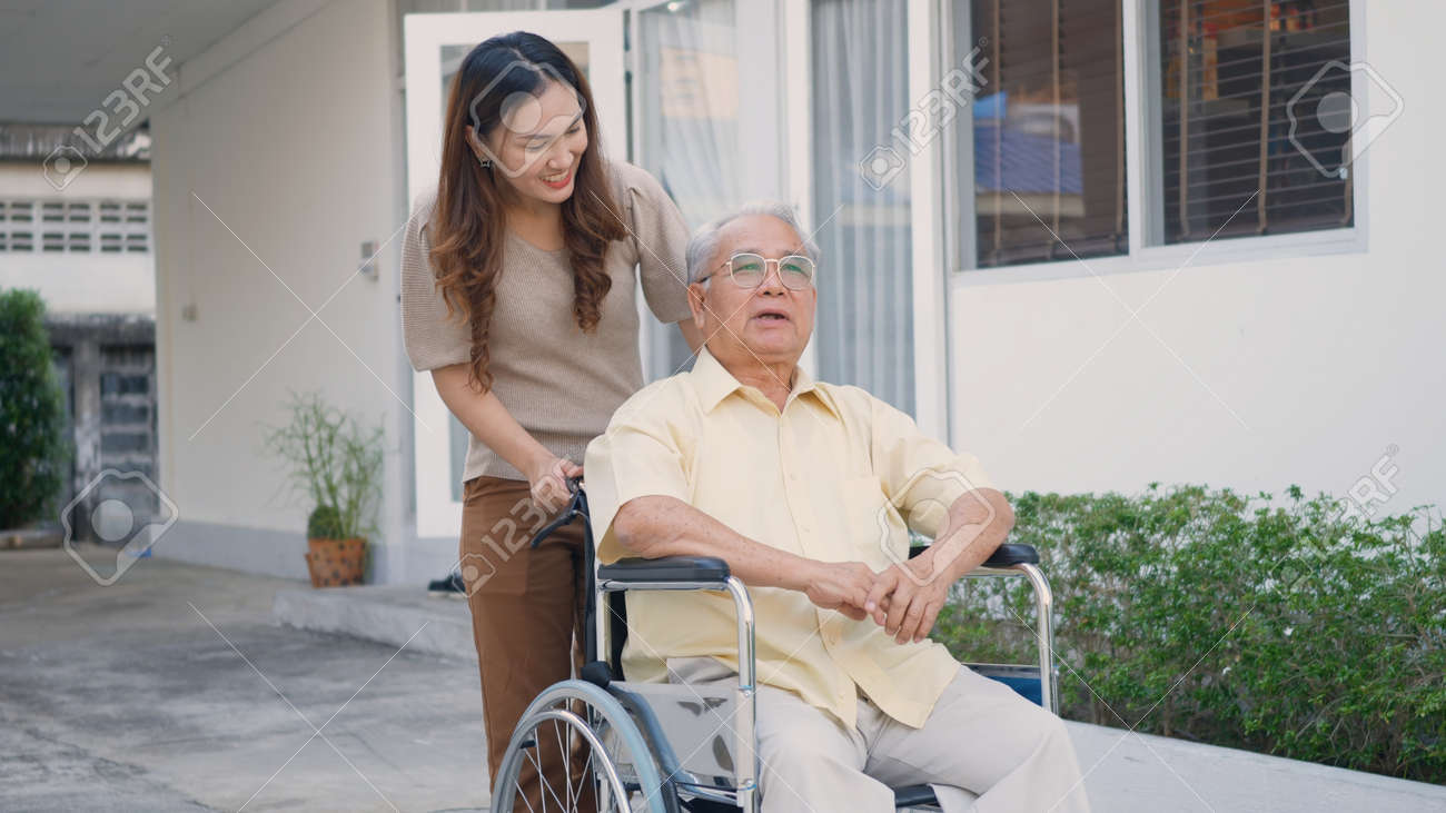 Disabled senior man on wheelchair with daughter, Happy Asian generation family having fun together outdoors backyard, Care helper young woman walking an elderly man smiling and laughed - 169945528