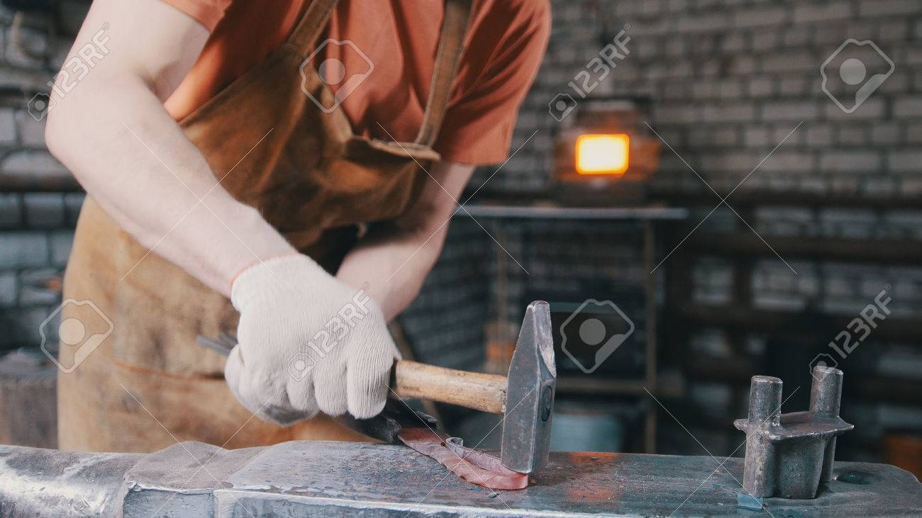 The smith gives shape with a hammer to a red-hot metal object