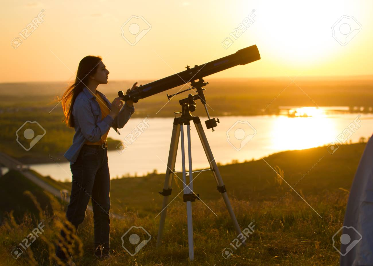 Silhouette of young woman looking view through the telescope at summer sunset - 101584271