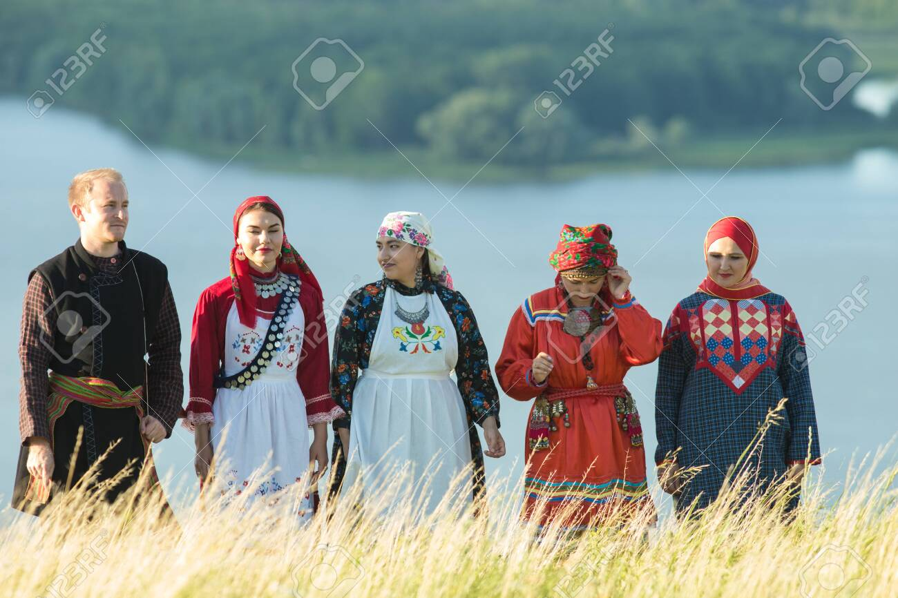 People in traditional russian clothes standing on the field - a man holding a balalaika - 126064196