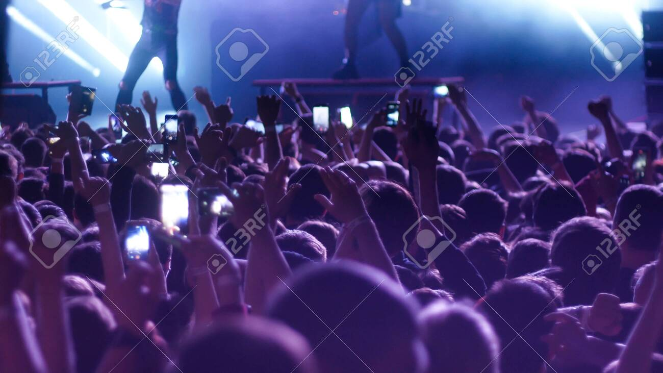 Energetic people dancing with their hands up at the concert. Mid shot - 135652990