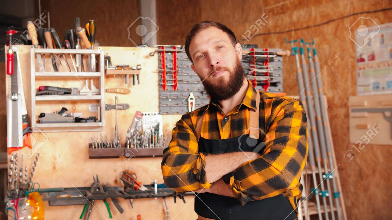 Bearded man worker in yellow shirt standing in the workshop - crossing his hands - 144859716
