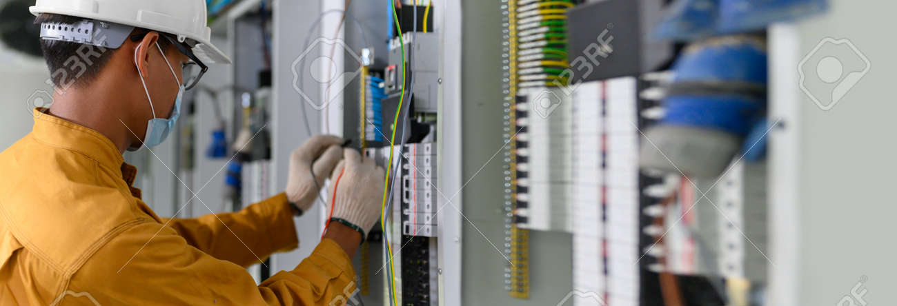 Electrician engineer using digital multimeter test current electric in control panel for testing electrical installations and wiring work in power control room on new building. - 171979145