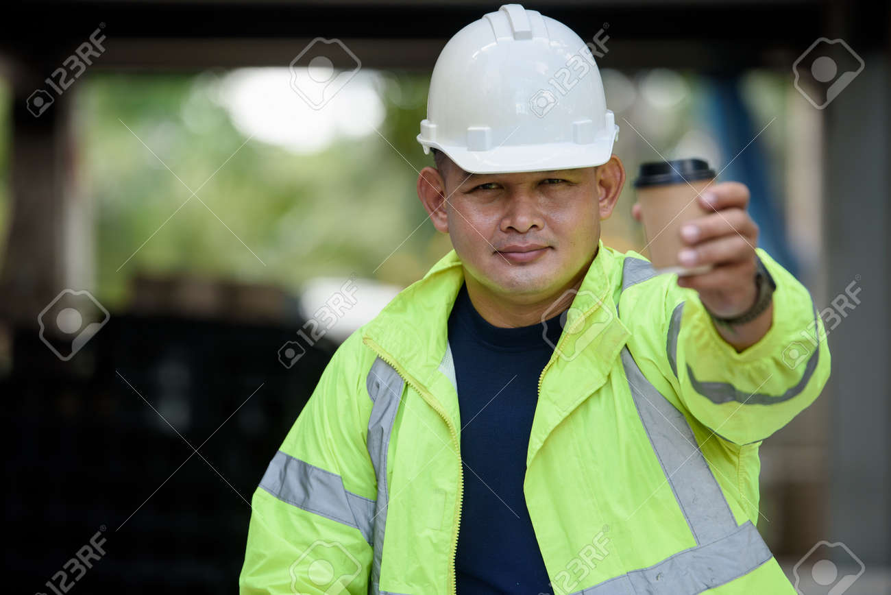 Construction engineer in reflective unifrom safety holds a cup hot coffee and hand to camera before work begins. - 171979146