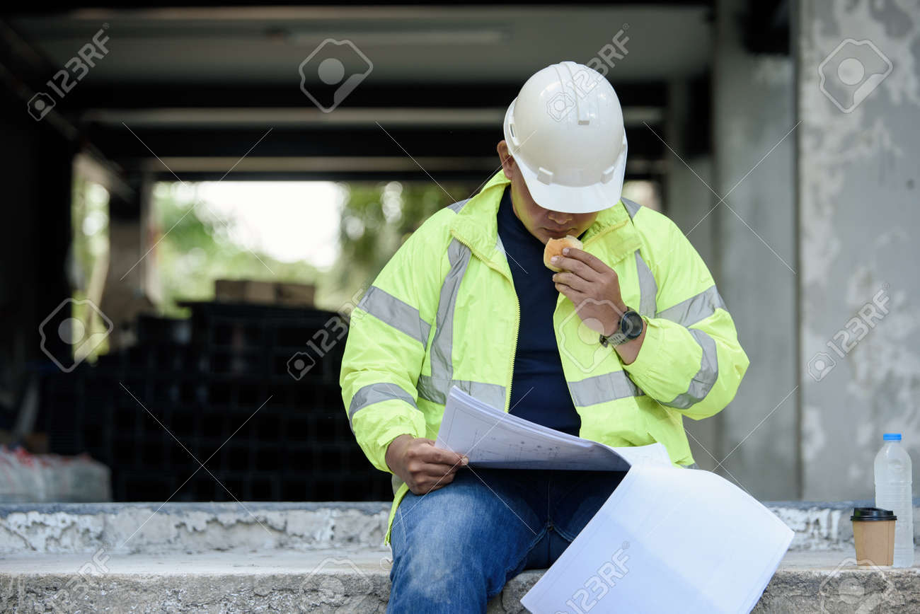 Civil Engineer sitting eats small bread in break time and reading building drawing with construction materials stock in background while hot weather at construction site during the day. - 171979151