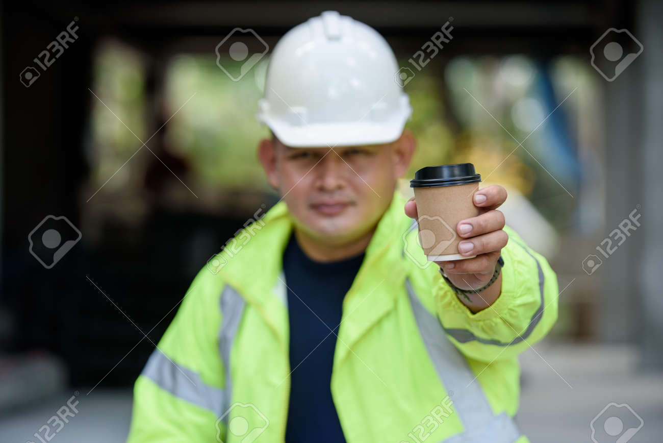 Construction engineer in reflective unifrom holds a cup hot coffee and hand to camera before work begins. Selection focuses on the cup of coffee. - 171979155