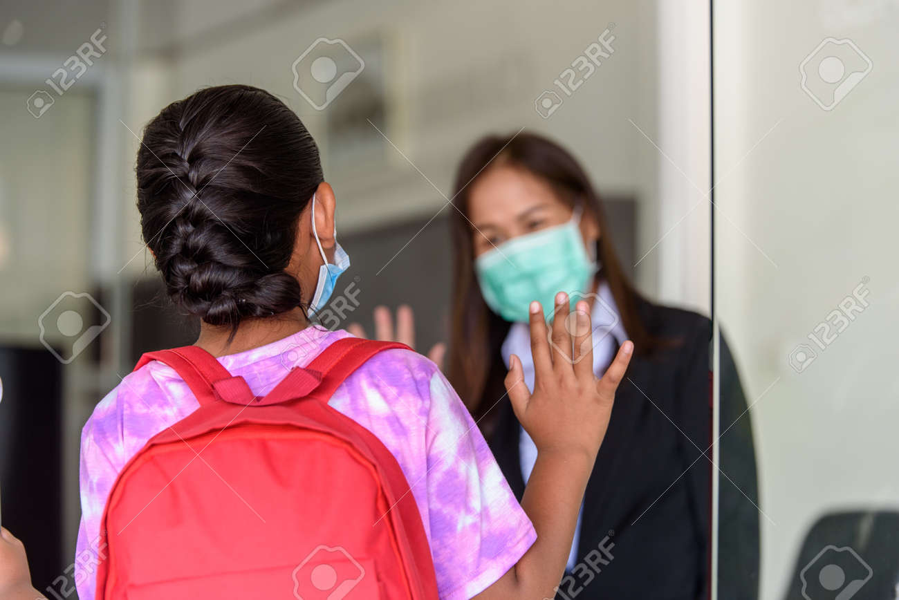 Student girl kids in medical face mask and raising their hand to greet teacher at Tutor school entrance door, Student screening before walk in classroom. - 171979156