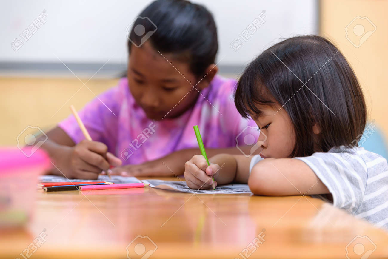 Asian little girl group sitting practice their skills and focus on coloring paper on table. Preschoolers learning at home to write and reading, Art education and creativity, Children's activities. - 171975362