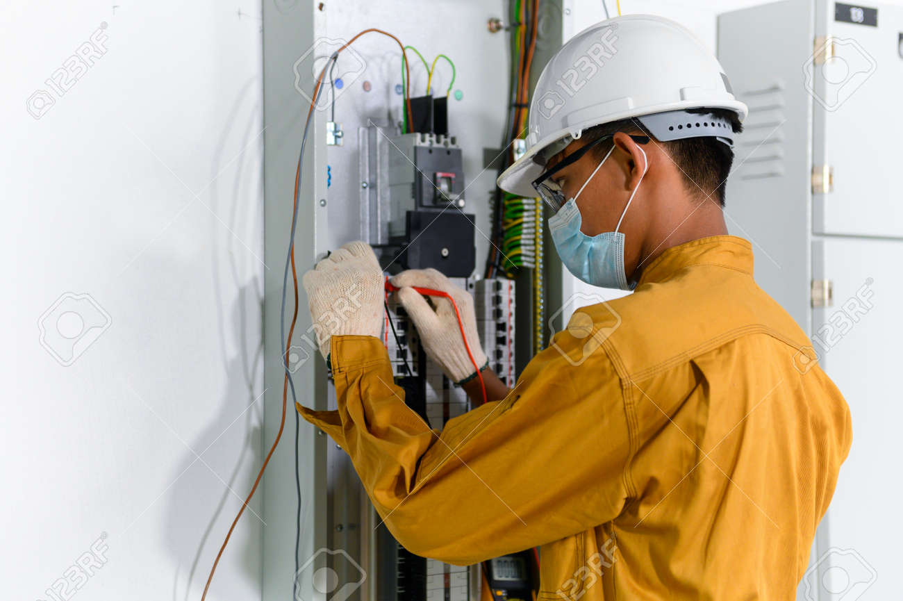 Electrician engineer using digital multimeter test current electric in control panel for testing electrical installations and wiring work in power control room on new building. - 171975364