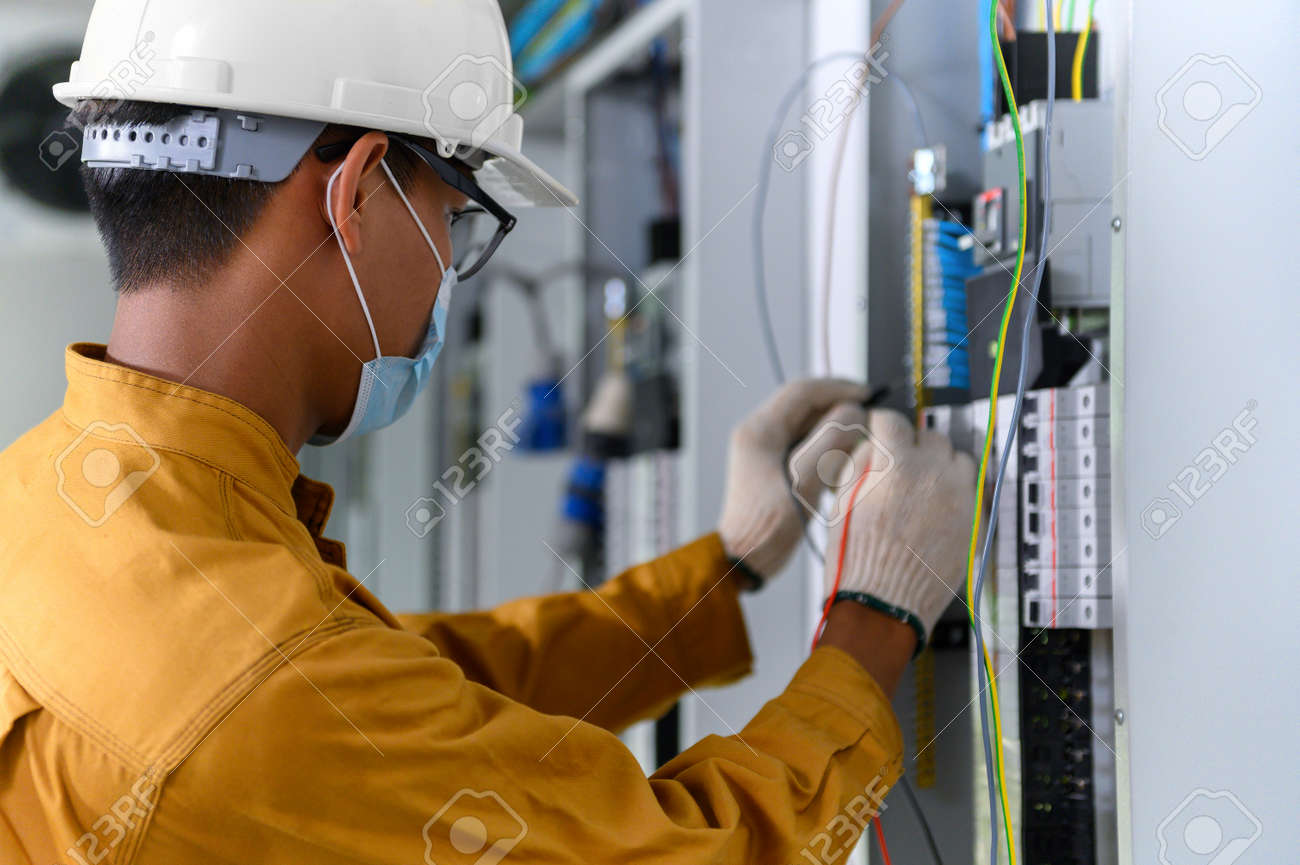 Electrician engineer using digital multimeter test current electric in control panel for testing electrical installations and wiring work in power control room on new building. - 171974374