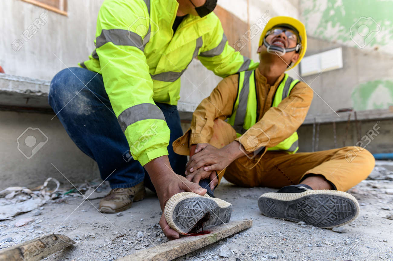 Builder worker has an accident at work. His feet stepped on nails embedded in wood old with foreman rushed in to take care. First aid and Safety in work concept. - 171974381