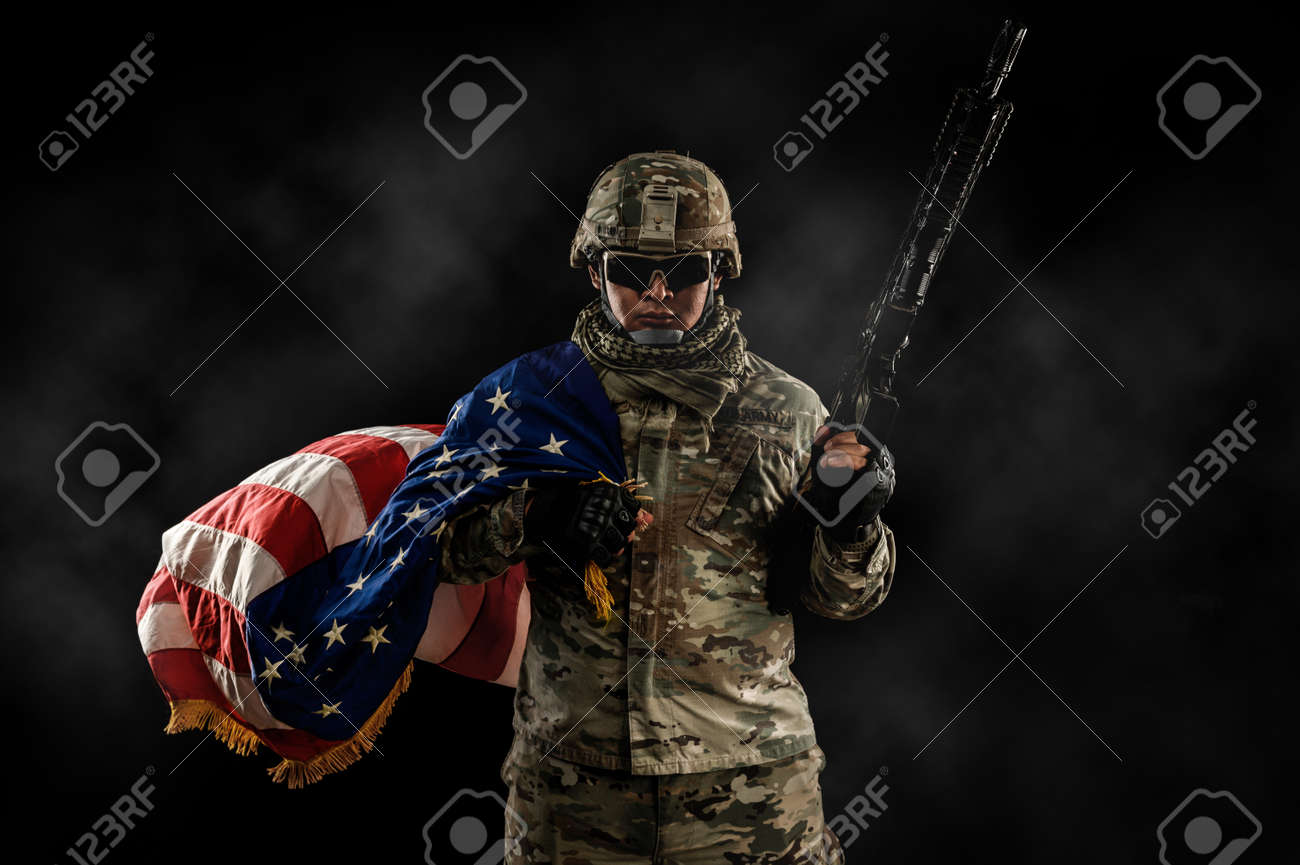 US Army soldier in combat uniforms holding the national flag across the shoulder and machine gun in smoke on dark background. Veterans Day, Patriot concept and Independence Day (United States) or ID4 - 171974309