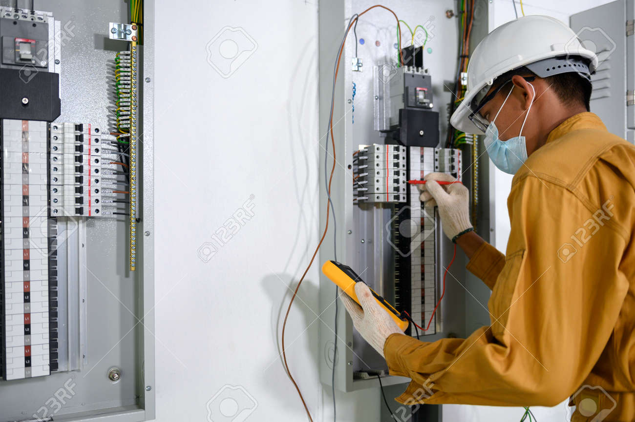 Electrician engineer using digital multimeter test current electric in control panel for testing electrical installations and wiring work in power control room on new building. - 171974315