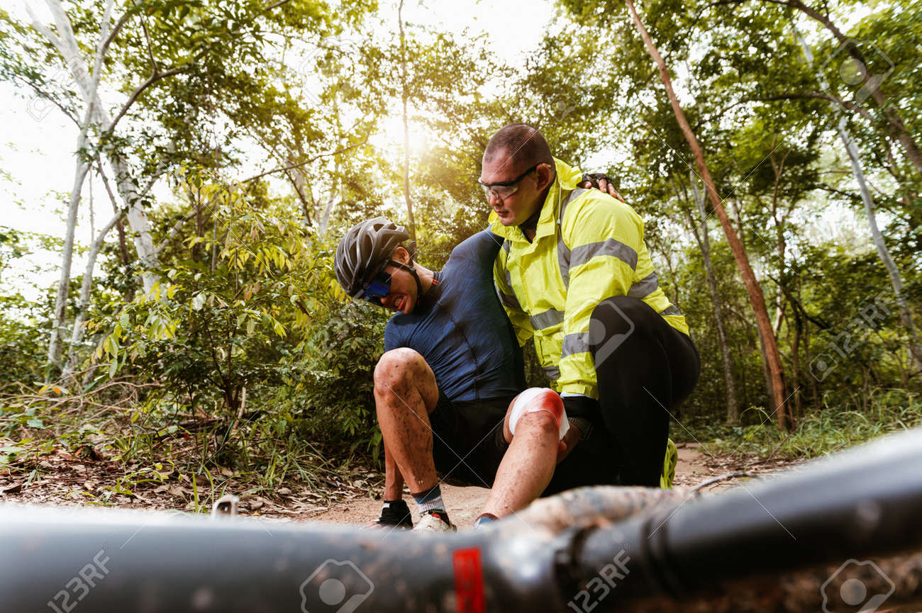Cyclist accident falling off mountain bike and knee injury and first aid at MTB track. Athlete accident in crash and dangerous on trail in forest. - 171974324