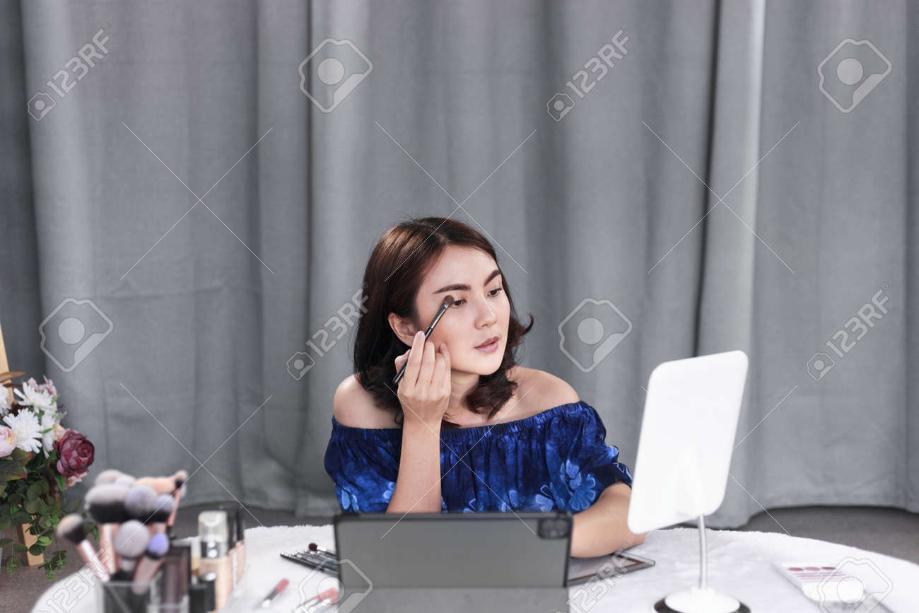Asian woman beauty blogger recording an easy guide for beginners of cosmetic brushes with makeup product and sharing on social media online with tablet at home. Selective focus on brushes - 171922465