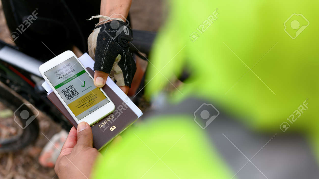 Disease immunity passport, Athlete uses application on smartphone show an international certification of vaccination at field entrance with Immunity passport and vaccination record card - 171922468
