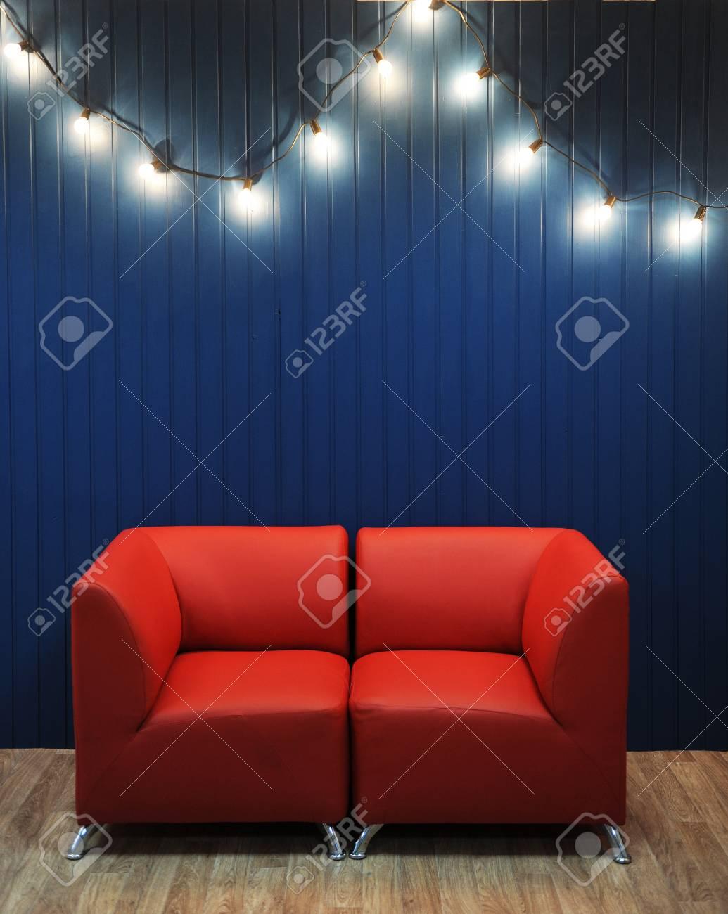 Divano Di Pelle.Divano Di Pelle Rossa Su Uno Sfondo Di Parete Blu Con Ghirlanda Retro Di Lampadine Interni Moderni Struttura Per La Progettazione