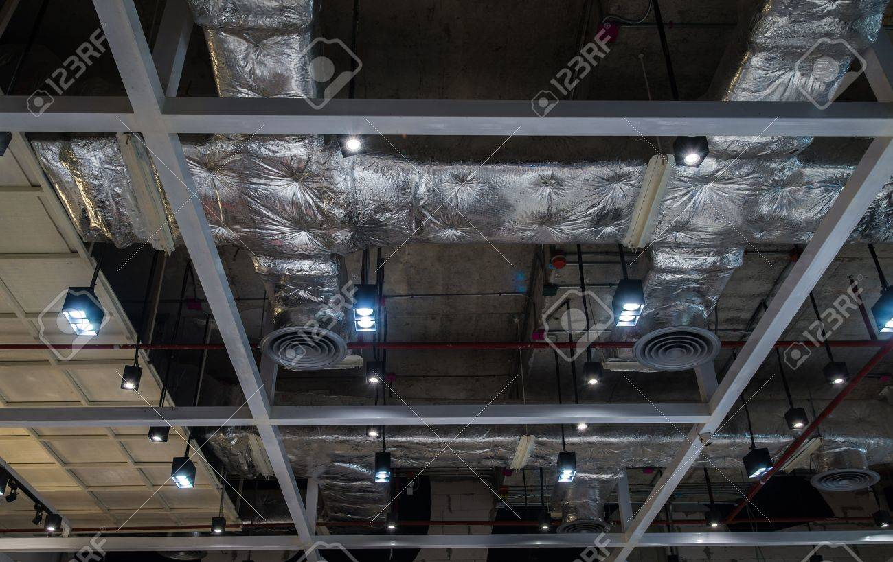 Ventilation system pipes on the ceiling of a modern factory plant building. - 48539934