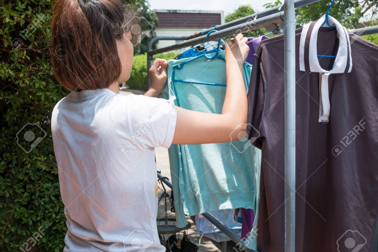 Woman hanging clothes on dryer at home. - 59159675