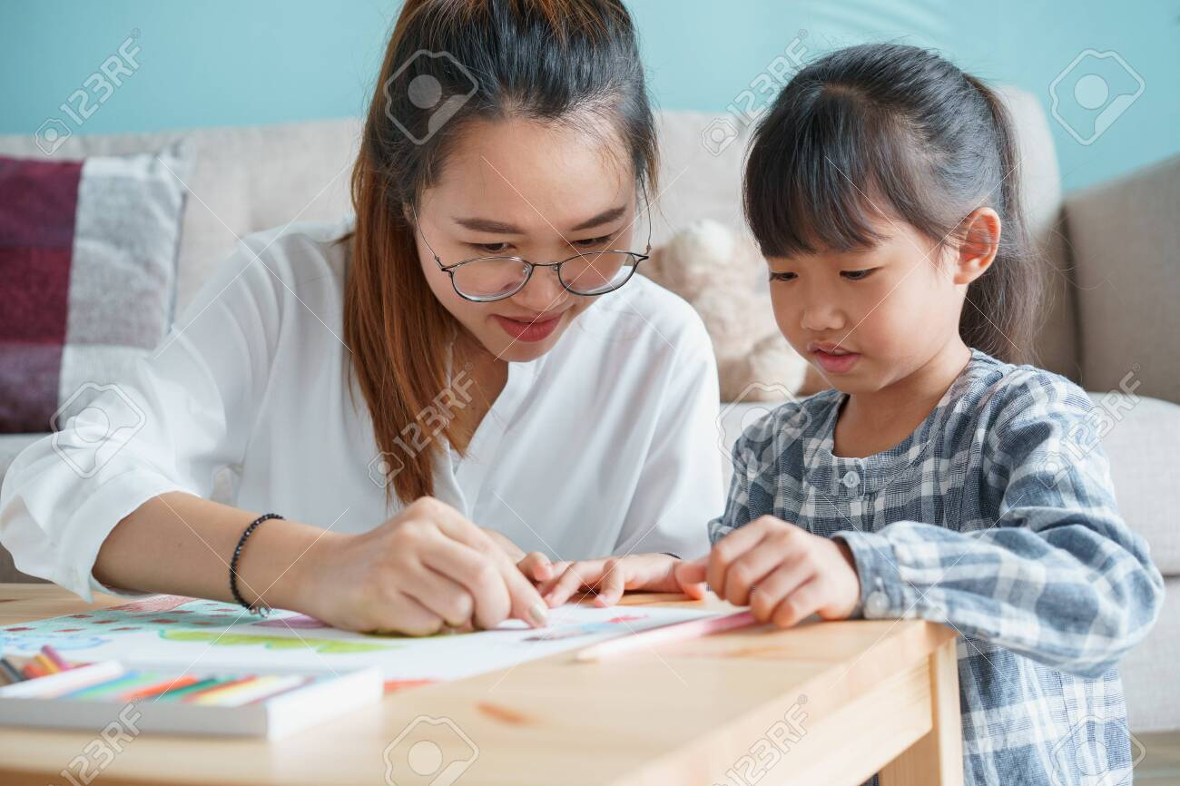 Asian family with mother and daughter doing together activities at home. happy mom and child doing learning and drawing on table in the living room in the morning - 153206941
