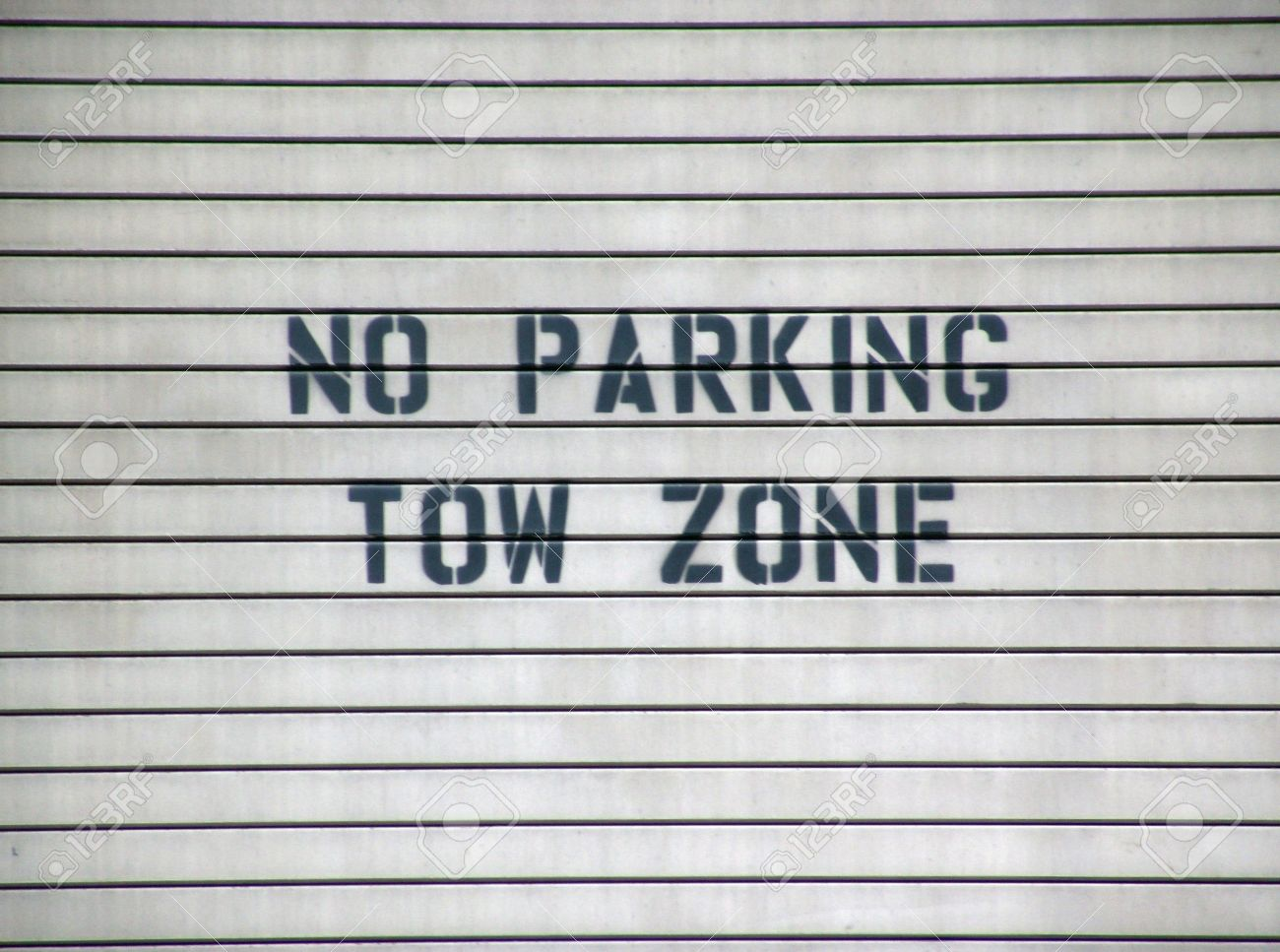 Garage Door Sign No Parking Tow Zone Black On Gray With Slats Stock
