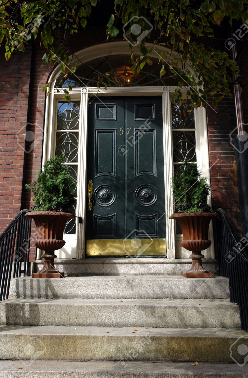 Stock Photo   Wide Black Door With Brass Kick Plate, White Wood Work And  Terra Cotta Flower Urns