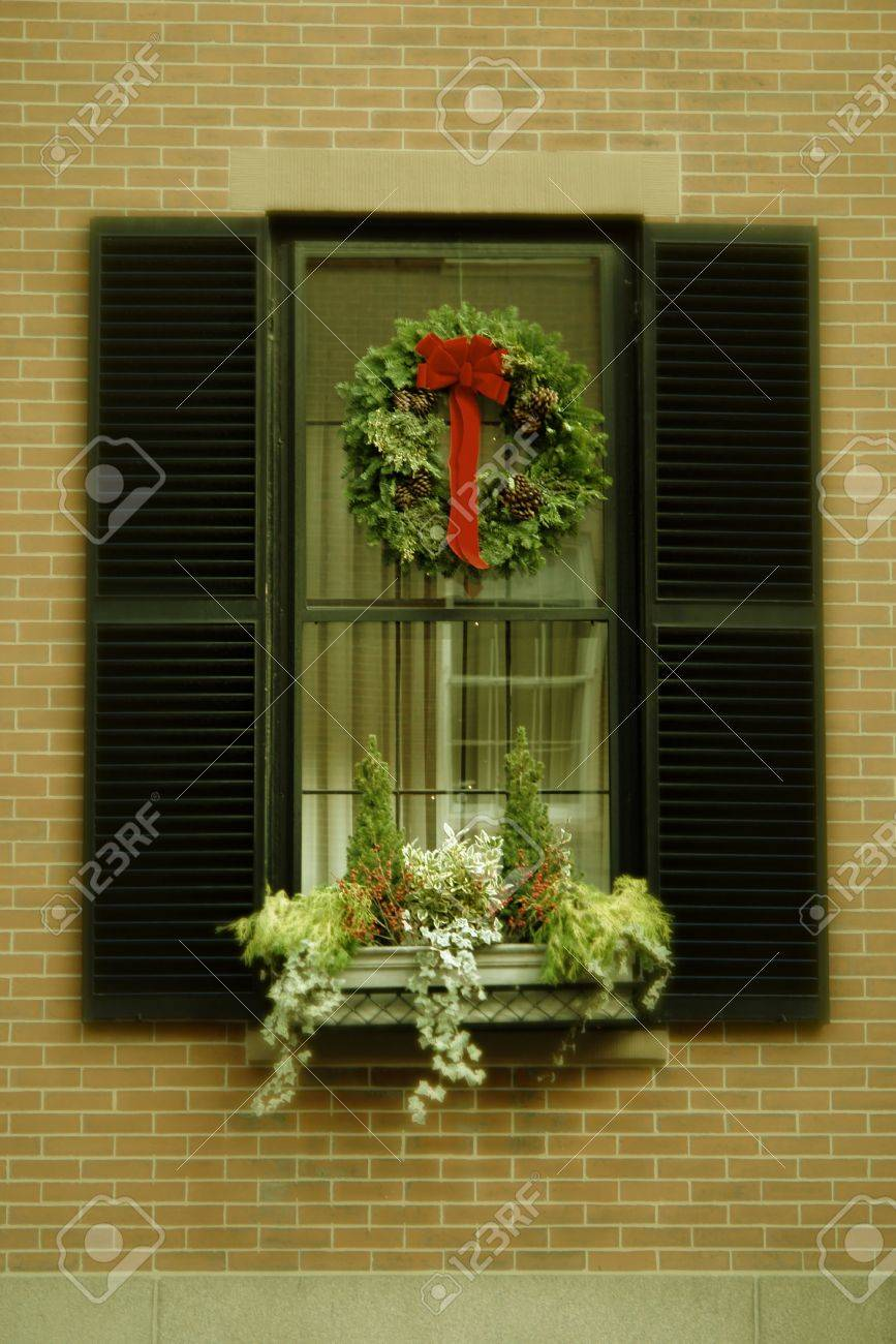 christmas wreath hanging in window of brick apartment building with flower box below antiqued colors