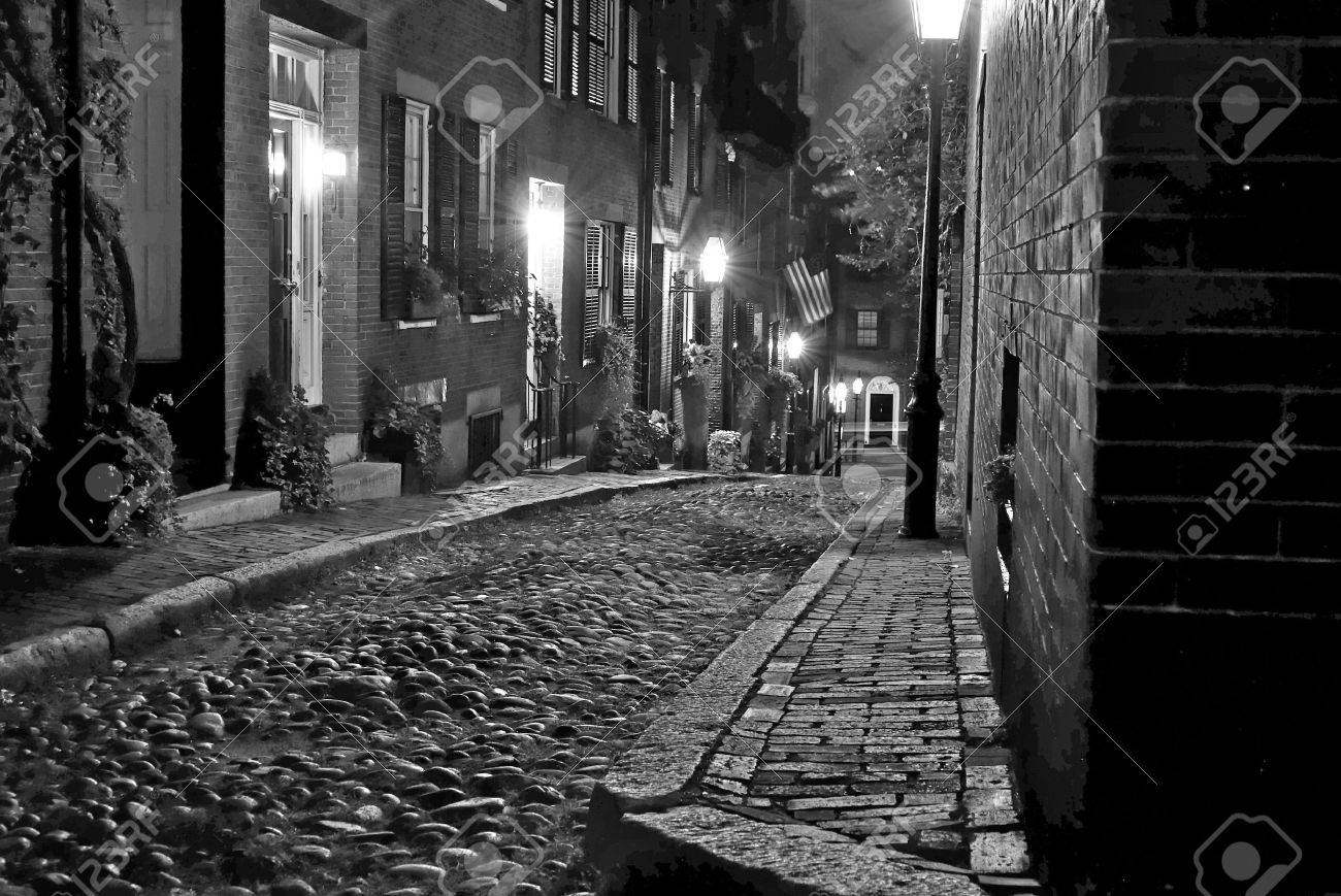 Black and white image of an old 19th century cobble stone road in boston massachusetts lit only by the gas lamps revealing the shuttered windows and