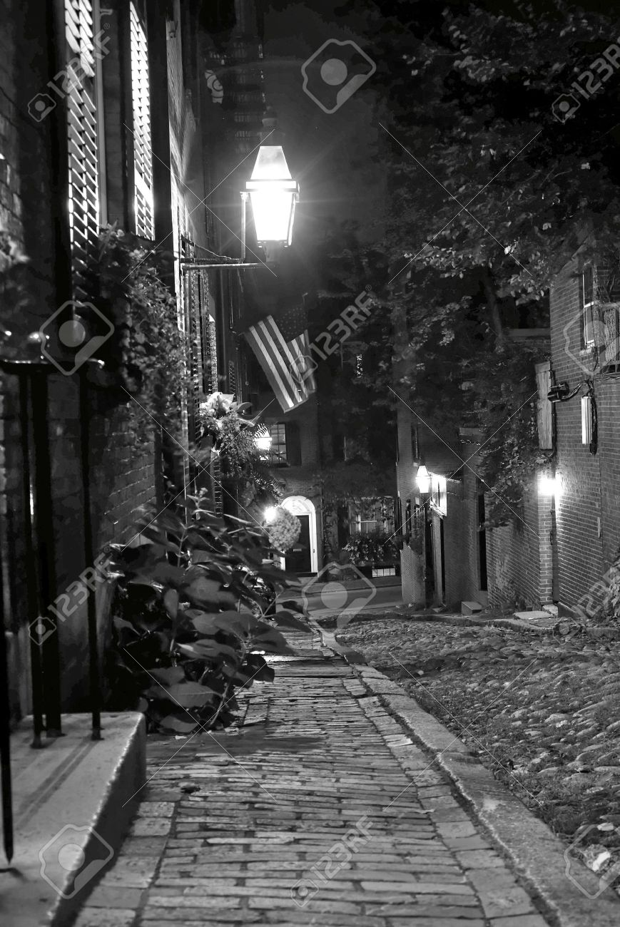 Black and white night image of an old 19th century cobble stone road in boston massachusetts lit only by the gas lamps revealing the shuttered windows and